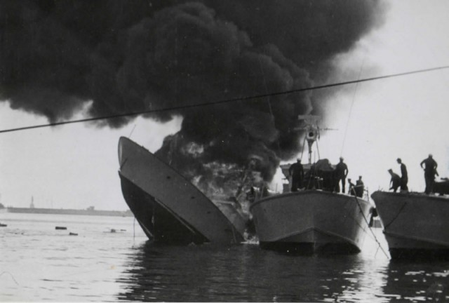 With flames engulfing the starboard side of HMS Gay Archer, P1023 begins to settle.